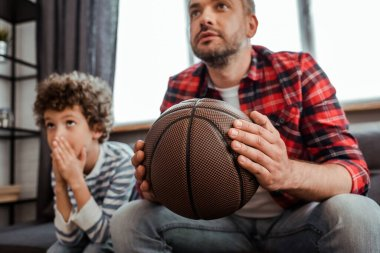 Selective focus of father holding basketball while watching championship with son stock vector