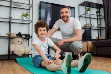 Cheerful man smiling near happy son on fitness mat stock vector