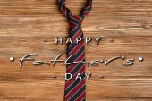 Horní pohled na pánské pruhované tkaniny kravaty na dřevěném pozadí, šťastný otců den ilustrace