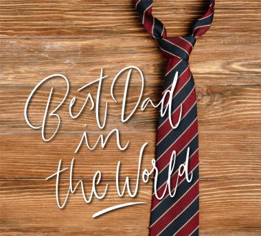 Top view of mens striped fabric tie on wooden background, best dad in the world illustration stock vector