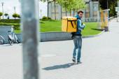 Selektivní zaměření na usměvavý doručovatel s termálním batohem chůze na městské ulici