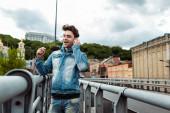 Selektivní zaměření usměvavý muž pomocí sluchátek na městské ulici