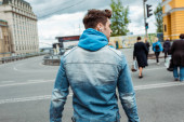 Back view of man in earphones walking on crosswalk on urban street