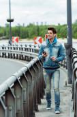 Photo Selective focus of positive man holding cellphone while walking near railing on bridge