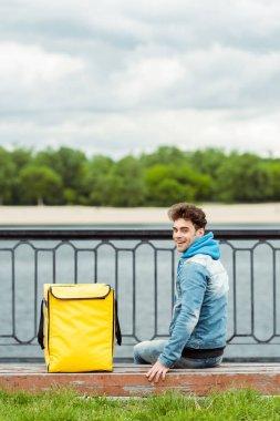 Gülümseyen kuryenin arka planı gezinti güvertesindeki bankta termo çantanın yanında oturuyor.