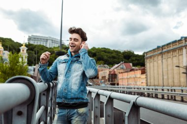 Selective focus of smiling man using earphones on urban street stock vector