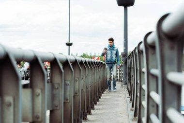 Selective focus of handsome man using smartphone while walking on bridge walkway stock vector