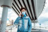 Muž v lékařské masce mluví na smartphone na městské ulici