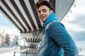 Oldalnézet pozitív férfi mosolyog a kamera a városi utcában