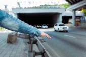 Oříznutý pohled stopaře zastavujícího auto u silnice
