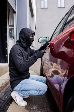 Side view of robber in balaclava using screwdriver while opening lock on door of car on urban street stock vector
