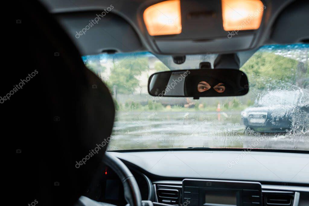 Focus selettivo dell'uomo in passamontagna guardando lo specchio in auto