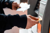 Cropped view of thief holding credit cards while using automated teller machine