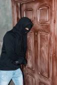 Burglar in mask breaking door lock with screwdriver
