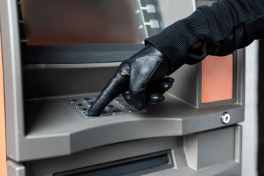Cropped view of burglar in leather glove using atm stock vector