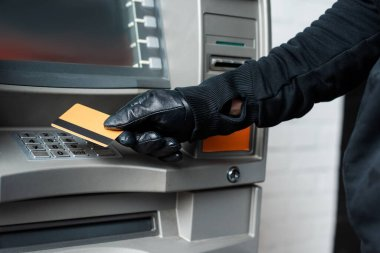 Cropped view of burglar in leather glove holding credit card near atm