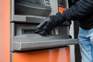 Cropped view of burglar in leather glove holding hand near cash dispenser of automated teller machine stock vector