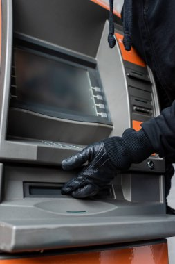 Cropped view of thief in leather glove holding hand near cash dispenser of atm stock vector