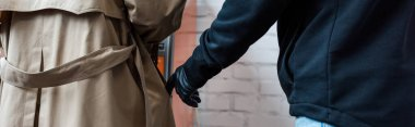 Panoramic shot of robber in leather glove putting hand in pocket of female coat