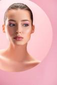 Porträt einer schönen nackten Frau mit glänzendem Make-up, die durch ein rundes Papierloch auf rosa isoliert blickt