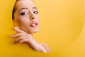 portrét krásné nahé ženy s lesklým make-upem v papírové kruhové díře s rukou izolovanou na žluté