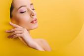 portrét krásné nahé ženy s lesklým make-upem v papírové kulaté díře s rukou a zavřenýma očima izolované na žluté