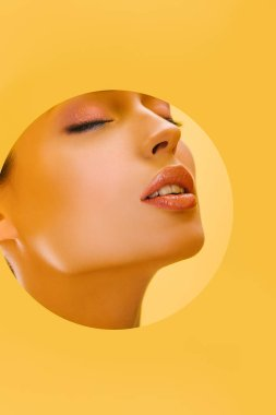 Portrait of beautiful woman with shiny makeup in paper round hole with closed eyes isolated on yellow stock vector