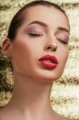 portrét krásné ženy s lesklým make-upem a zavřenýma očima na zlatém pozadí