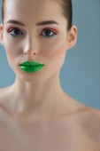 portrait of beautiful naked woman with green lips, pink and blue eyeshadow isolated on blue