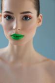 Porträt einer schönen nackten Frau mit grünen Lippen, rosa und blauem Lidschatten isoliert auf blau