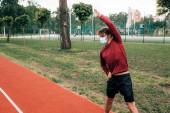 Fotografie Sportler mit medizinischer Maske trainiert auf Bahn im Park