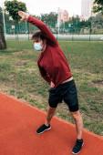 Fotografie Sportler mit medizinischer Maske trainiert auf Laufbahn im Park