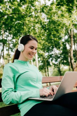 Smiling freelancer listening music in headphones and using laptop in park