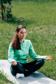 Photo Attractive woman meditating on fitness mat on grass in park