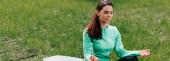 A fitneszszőnyegen meditáló fiatal nő panoráma termése a parkban