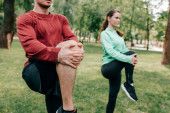 Selective focus of couple stretching legs while working out in park