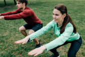 Selective focus of smiling sportswoman doing squat while working out near boyfriend in park