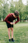 Young sportsman pulling up resistance band on lawn in park