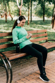Photo Smiling sportswoman in headphones using smartphone near sports bottle on bench in park
