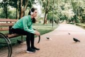 Boční pohled sportovkyně ve sluchátkách sedí v blízkosti sportovní láhve a smartphone na lavičce v parku
