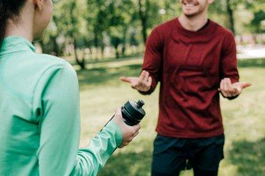Cropped view of sportswoman holding sports bottle near smiling boyfriend in park stock vector