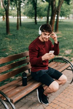 Smiling sportsman in headphones using smartphone while sitting near sports bottle on bench in park