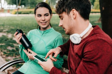 Selective focus of smiling sportswoman holding sports bottle near boyfriend using smartphone on bench in park