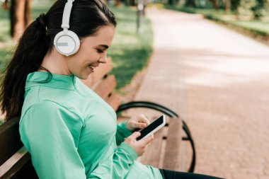 Side view of smiling sportswoman in headphones using smartphone on bench in park
