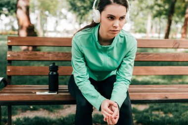 Sportswoman in headphones sitting near smartphone and sports bottle on bench in park