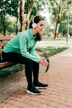 Side view of young sportswoman in headphones resting on bench in park
