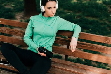 Beautiful sportswoman in headphones holding sports bottle while resting on bench in park
