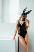 Photo Sensual woman in bodysuit and bunny mask standing on white background