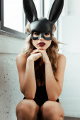 Photo Young woman in rabbit mask looking at camera near window
