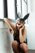 Photo Young woman in bunny mask laughing near window